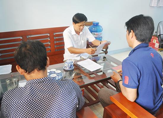 Chủ tịch UBND xã Dang (huyện Tây Giang) Nguyễn Thanh Tâm tiếp dân giải quyết công việc tại cơ quan. Ảnh: HÀN GIANG