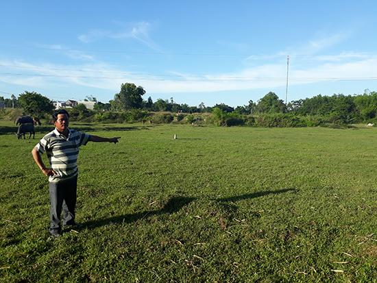 Ông Phú bên cạnh đám ruộng không sản xuất được từ nhiều năm nay vì không có mương dẫn nước.