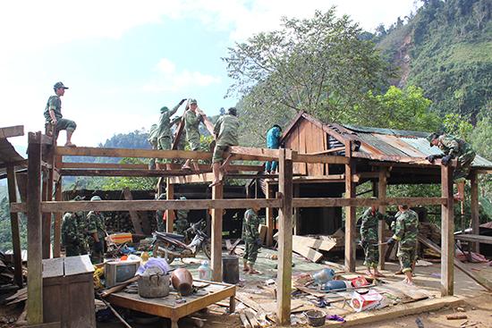 Cán bộ, chiến sĩ Bộ CHQS tỉnh giúp dân tháo dỡ nhà cửa di chuyển đến nơi ở mới. Ảnh: T.ANH