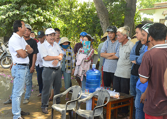 Ông Phan Minh Dũng - Phó Chủ tịch UBND thị xã Điện Bàn (đội mũ vải) đối thoại với người dân địa phương về những vướng mắc trong thi công nâng cấp, mở rộng tuyến ĐT607. Ảnh NGUYÊN ĐOAN