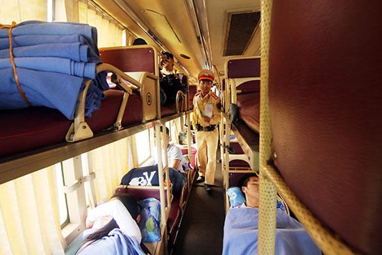 Cán bộ Trạm CSGT Thăng Bình kiểm tra việc vận tải hành khách trên tuyến quốc lộ 1.Ảnh: THÀNH CÔNG