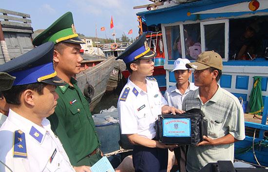 Cảnh sát biển xuống tận tàu cá, trao tặng túi thuốc và nhiều phần quà cho ngư dân Lý Sơn. Ảnh: T.C