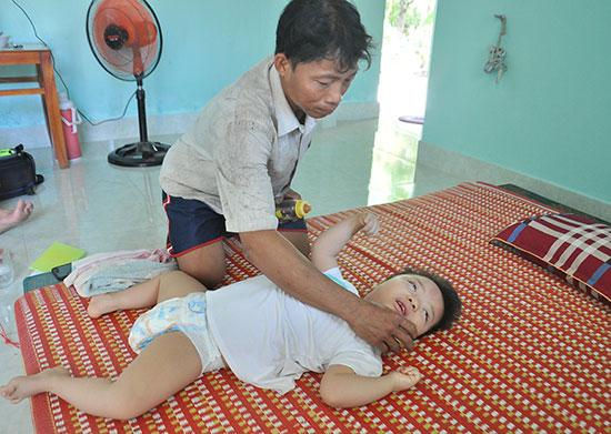Anh Nguyễn Thanh Liêm chăm sóc con gái bị bệnh bại não. Ảnh: VINH ANH