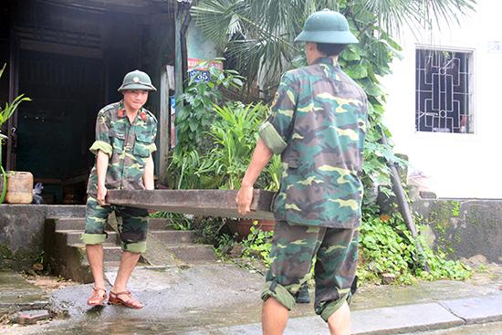 Các chiến sĩ Ban CHQS Bắc Trà My giúp người dân dọn dẹp bùn đất sau đợt lũ tháng 11.2017. Ảnh: T.L