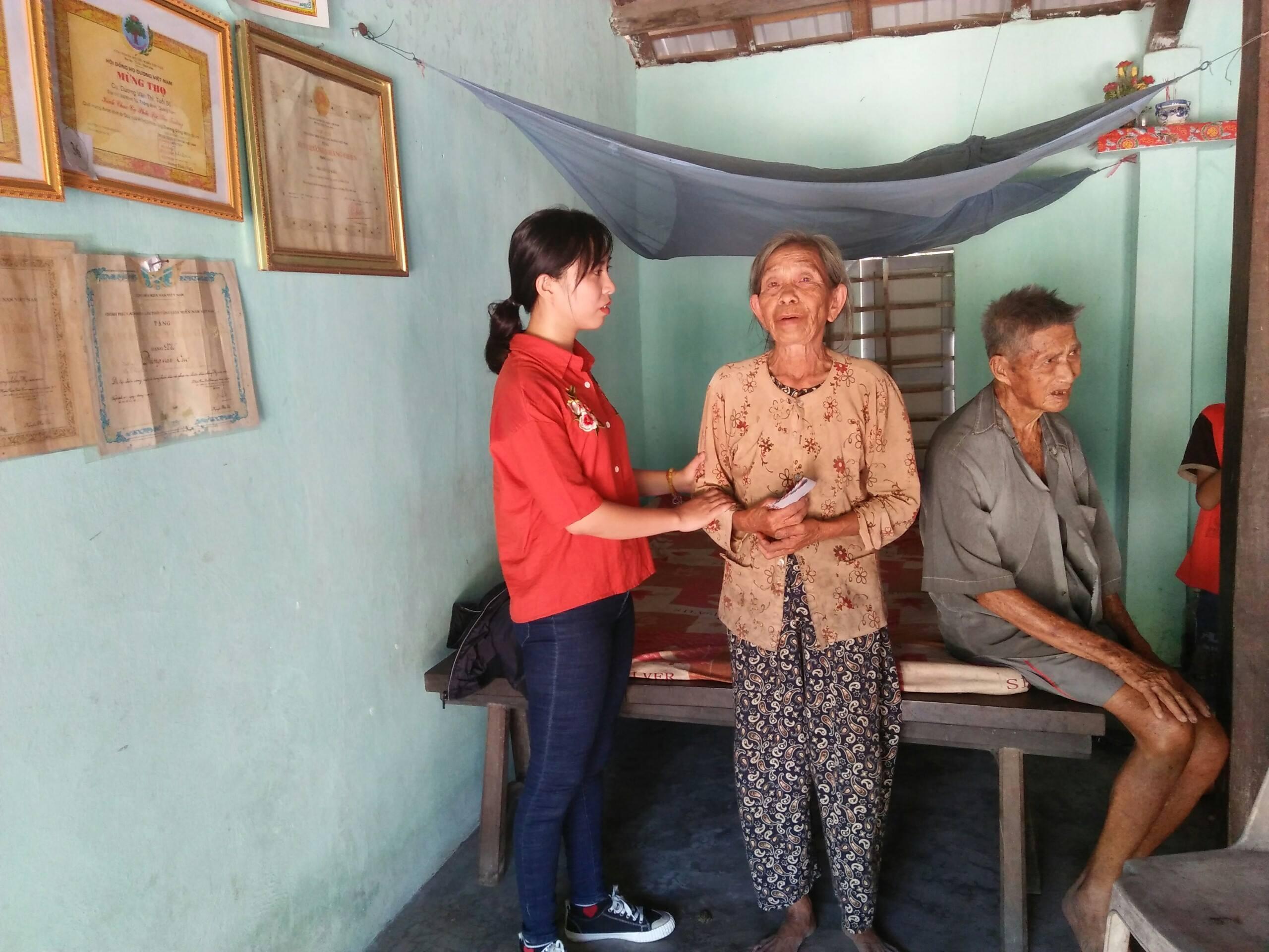 Tác giả bài viết (trái) trao tiền hỗ trợ bà Kiểu. Ảnh: L.L