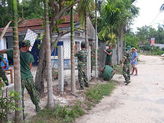 Có bộ đội giúp, gia đình ông Nguyễn Ngọc Vấn hăng hái di dời tường rào vào bên trong 1m để mở rộng đường trục chính thôn. Ảnh: T.Q