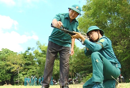 Chính trị viên Lê Xuân Long (bên trái) hướng dẫn thao tác bắn súng cho chiến sĩ dân quân. Ảnh: XUÂN SƠN