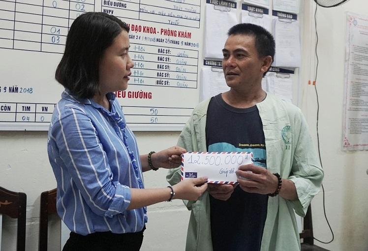 Đại diện gia đình em Nguyễn Đức Phú nhận số tiền bạn đọc Báo Quảng Nam gửi ủng hộ. (ảnh: Như Trang)