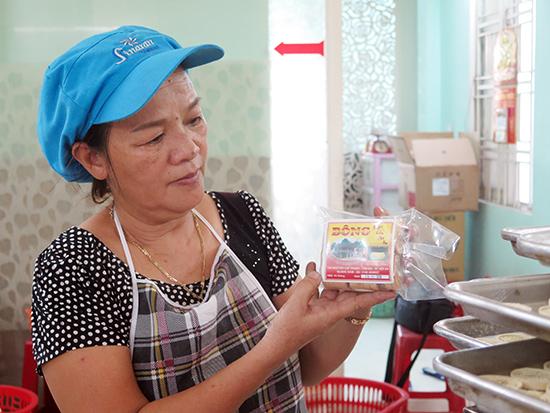 Bà Nguyễn Thị Bông và sản phẩm bánh đậu xanh tham gia vào chương trình OCOP của Hội An. Ảnh: X.HIỀN