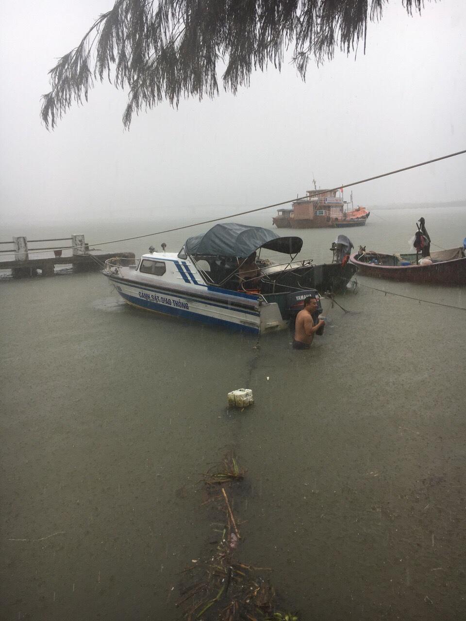 Cảnh sát đường thủy dầm trong mưa lớn, hỗ trợ bảo vệ tàu thuyền, di dời người dân. Ảnh: T.C