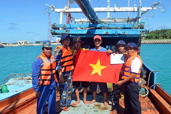 Chỉ huy Trung tâm Hậu cần - kỹ thuật đảo Sinh Tồn cấp cờ Tổ quốc cho tàu cá. Ảnh: CÔNG HOAN