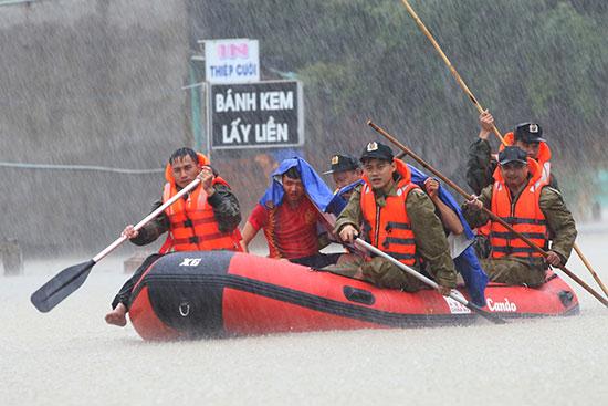 Chiến sĩ công an dầm mình trong mưa cứu dân ở huyện Phú Ninh đợt ngập lụt lịch sử vào đầu tháng 12 vừa qua. Ảnh: T.C