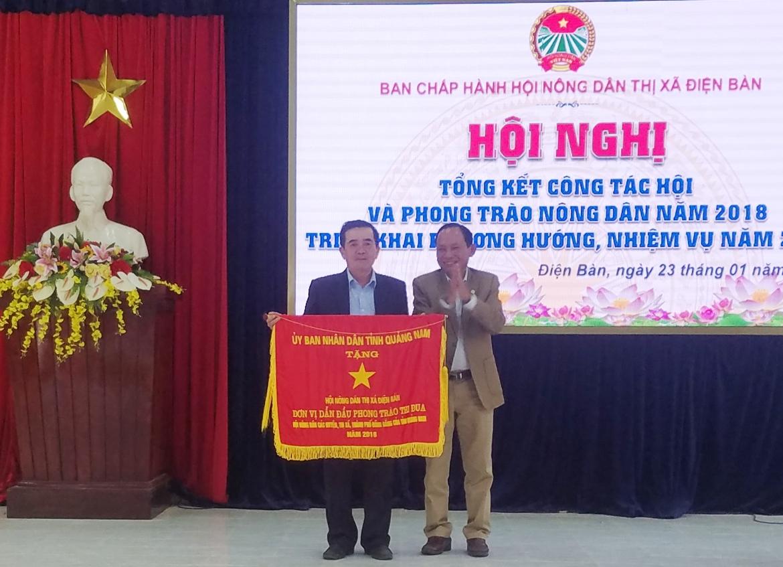 Ông Vũ Văn Thẩm - Chủ tịch Hội Nông dân tỉnh trao cờ thi đua của UBND tỉnh tặng cho Hội Nông dân Điện Bàn. Ảnh: Q.T
