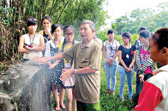 Ông Văn Công Mịch bạn chiến đấu của nhà văn Chu Cẩm Phong, đang kể lại phút cuối cùng anh hùng liệt sĩ Chu Cẩm Phong hy sinh. Ảnh: Quế Hà