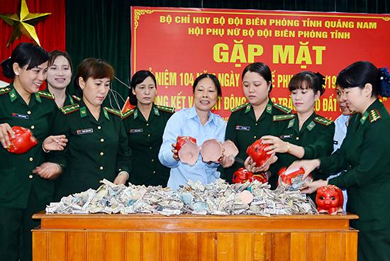 """Hội viên phụ nữ BĐBP tỉnh cùng """"mổ"""" heo đất, gây quỹ từ thiện. Ảnh: ALĂNG NGƯỚC"""