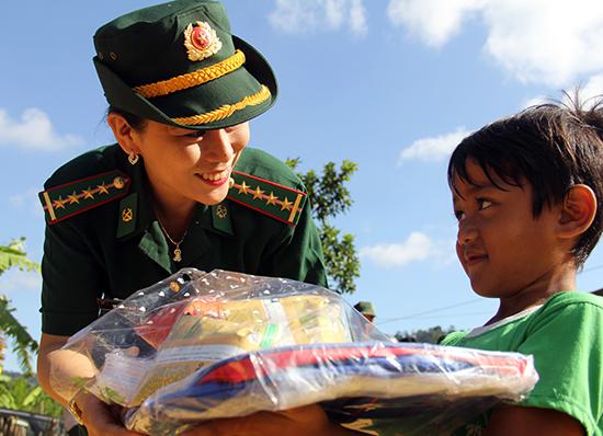 Nữ chiến sĩ BĐBP tỉnh trao quà cho trẻ em vùng cao, nhân dịp 1.6. Ảnh: ALĂNG NGƯỚC