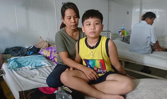 Em Lương Văn Hoàng (bên phải) đang điều trị tại Khoa Ngoại thần kinh, Bệnh viện Đà Nẵng. Ảnh: N.TRANG