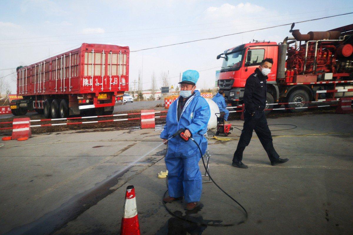 Một công nhân tại Trung Quốc  xịt thuốc khử trùng ngăn ngừa lây lan bệnh ASF. Ảnh: Reuters