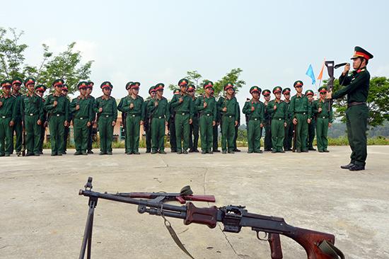 Cán bộ trung đội hướng dẫn động tác khám súng cho chiến sĩ mới. Ảnh: TUẤN ANH