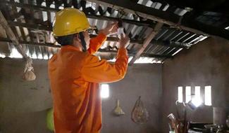 Giúp đỡ nhân dân thay thế bóng đèn chiếu sáng giúp tiết kiệm điện năng. Ảnh: T.D