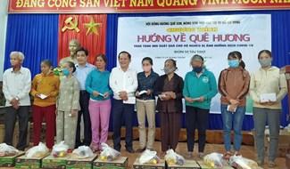 Phó Bí thư Tỉnh ủy Lê Văn Dũng và ông Mai Phúc - Chủ tịch Hội đồng hương Quế Sơn - Nông Sơn - Hiệp Đức trao tặng quà cho người nghèo Hiệp Đức. Ảnh: HOÀNG LIÊN